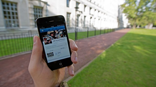 1024px-A_serviceman_accesses_social_media_channels_using_a_smart_phone,_outside_MOD_Main_Building_in_London_MOD_45156045