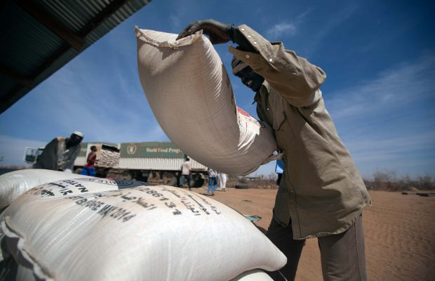 11 February 2014. Shangil Tobaya: A community member in Nifasha camp for Internally Displaced Persons (IDP), North Darfur, unloads a bag of sorghum from a World Food Programme (WFP) truck. Ten WFP trucks, with two containers each, traveled from El Fasher to Shangil Tobaya to deliver 350 metric tons of food (oil and sorghum) to Nifasha and Shaddad camps for Internally Displaced Persons.  WFP through its partner, Africa Humanitarian Action (AHA), provides food for around 20,000 beneficiaries in these camps, who have fled from different surrounding villages in the region; some 14km north of the South Darfur border and at the midpoint between El-Fasher and Nyala. WFP food remains the main source of food for IDPs in Shangil Tobaya.  The road trip, nearly 100 kilometers, took more than 8 hours due to difficult road conditions. The convoy was protected all the way by UNAMID troops from Ethiopia and Rwanda. Photo by Albert Gonzalez Farran, UNAMID.